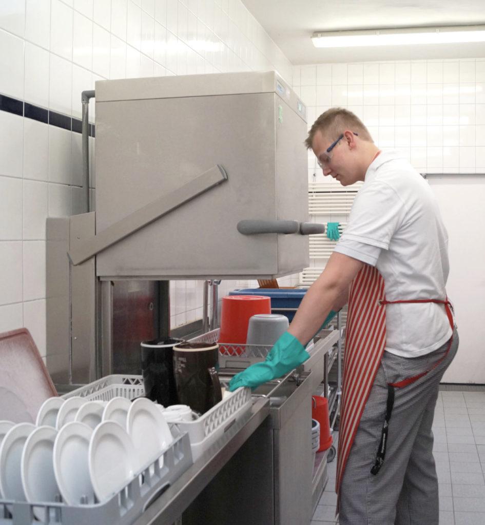 FSJler steht in der Küche in der Spülstraße und bedient die Spülmaschine