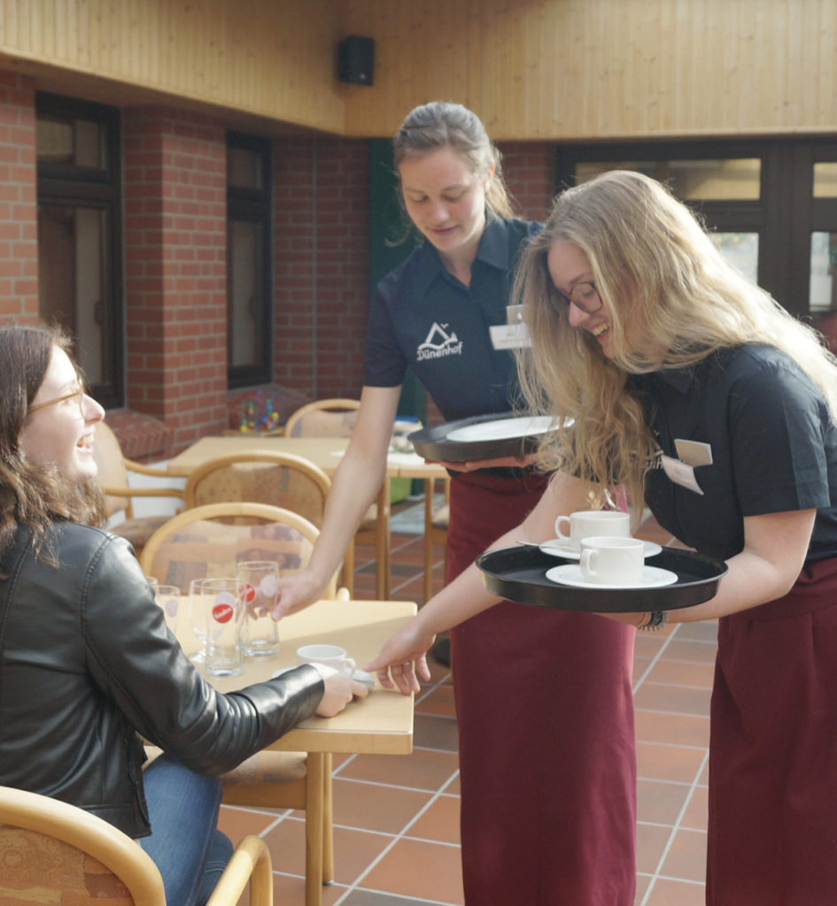 Zwei Junge Frauen servieren einer anderen jungen Frau etwas zu Trinken